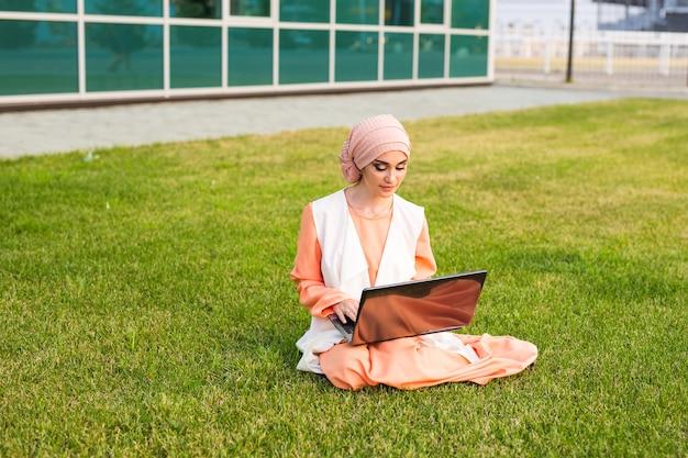 ノートブックと公園で美しいイスラム教徒の女性