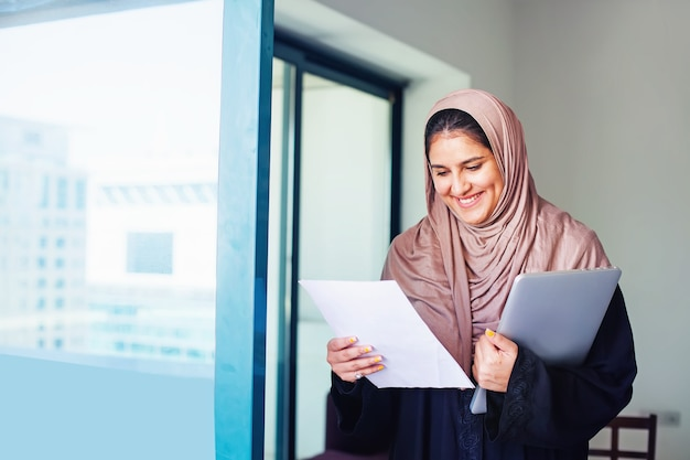 Beautiful muslim  woman in hijab holding laptop and documents