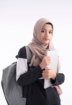 The beautiful muslim woman holding laptop in hand
