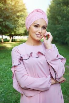 ピンクのドレスと緑の木々を背景にターバンの美しいイスラム教徒の女性