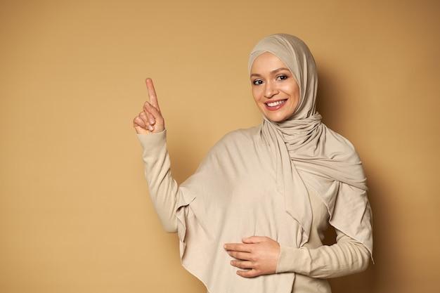 ヒジャーブと伝統的な衣装の美しいイスラム教徒の女性は、歯を見せる笑顔でかわいい笑顔で、正面を見ながらコピースペースでベージュの表面の側面に人差し指を置きます