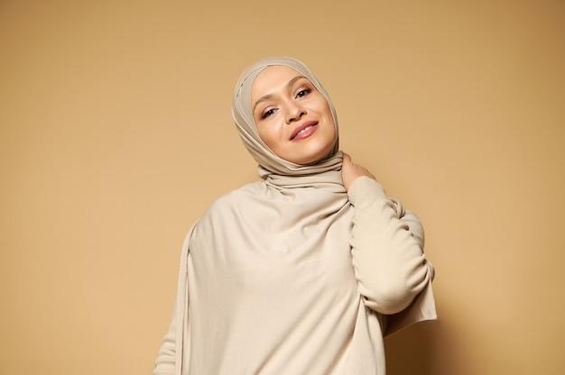 コピースペースでベージュの表面にポーズをとっている間ヒジャーブかわいい笑顔の美しいイスラム教徒の女性