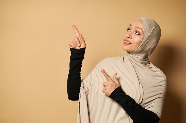 コピースペースでベージュの表面の側面に人差し指を向けるヒジャーブの美しいイスラム教徒の女性