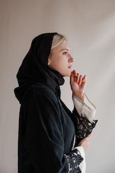 회색 배경에 전통적인 아라비아 아바야 드레스를 입은 아름다운 이슬람 여성