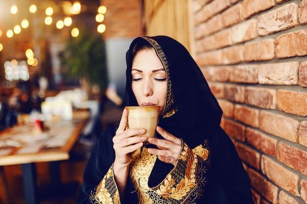 카페테리아에 앉아서 커피를 즐기는 전통적인 착용에 아름 다운 이슬람 여자.