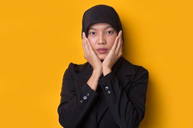 Красивая мусульманская женщина выглядит удивленной, изолированной на желтом