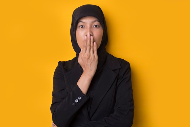 Beautiful muslim woman looking suprised isolated on yellow