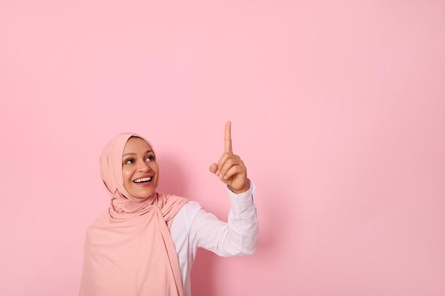 宗教的な衣装に身を包んだ中東民族の美しいイスラム教徒の女性は、ヒジャーブ民族の笑顔で頭を覆い、ピンクの背景のコピースペースに人差し指を上に向けて見上げます