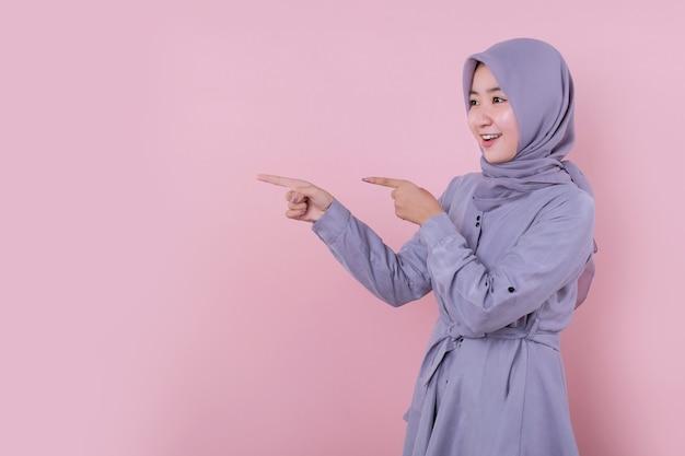 彼女の隣を指している美しいイスラム教徒の女性