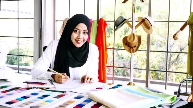 オフィスで服のシルエットをスケッチする美しいイスラム教徒の女性。