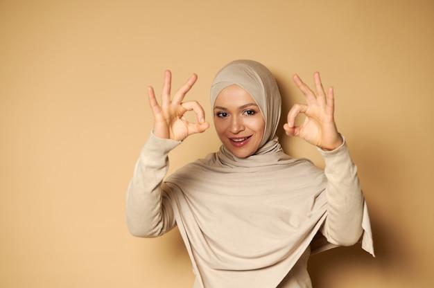 ヘッドスカーフまたはヒジャーブを身に着けている美しいイスラム教徒の女性は彼女の指でokを身振りで示し、コピースペースのあるベージュの表面にかわいい歯を見せる笑顔で正面を見る
