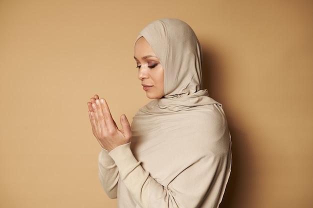ラマダンのために祈るヒジャーブと厳格な宗教的な衣装を身に着けている美しいイスラム教徒の女性