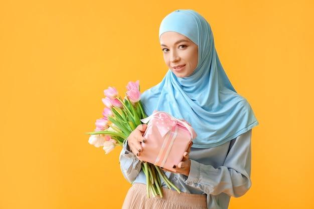 Красивая мусульманская женщина с цветами и подарком. празднование международного женского дня