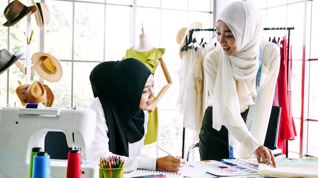 Beautiful muslim women sketching clothes silhouette together at the office.