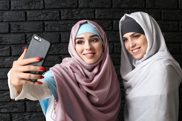 暗い背景でselfieを取る美しいイスラム教徒の女性