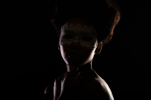 Beautiful mysterious american black female girl in a venetian mask isolated on black