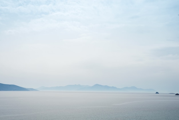 Beautiful mysterious nature background with of the ocean against the misty mountains