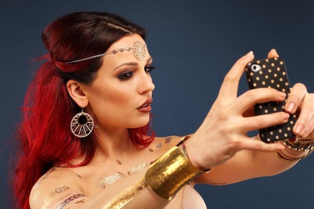 スマートフォンで美しい神秘的な東洋の女性