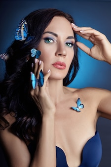 Beautiful mysterious woman with butterflies blue