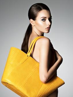 아름 다운 벗은 여자는 스튜디오에서 포즈 패션 핸드백을 보유