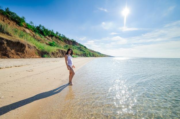 Красивая обнаженная женщина на берегу моря.