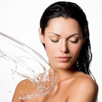 Bella donna nuda con il corpo bagnato e spruzzi d'acqua