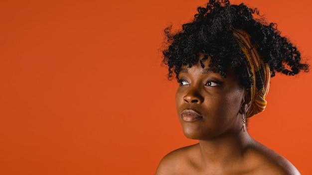 Beautiful naked young african american woman on colored background