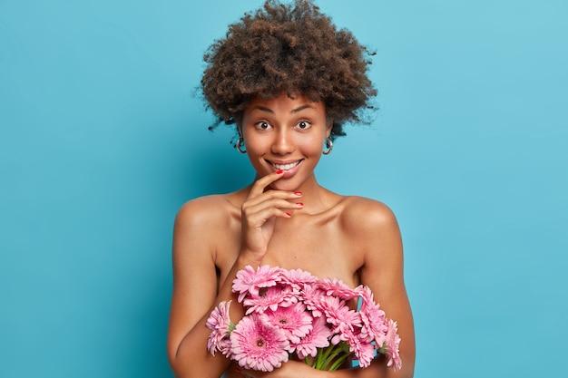 La bella giovane donna nuda con l'acconciatura afro tiene un bel mazzo di gerbere, ha una pelle sana e ben curata, posa