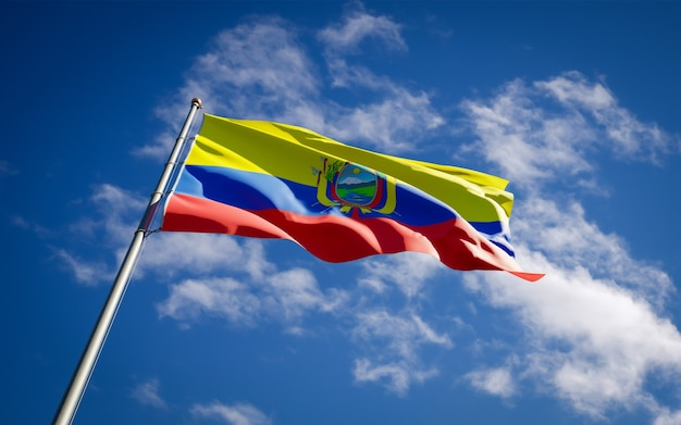 Beautiful national state flag of ecuador fluttering on blue sky