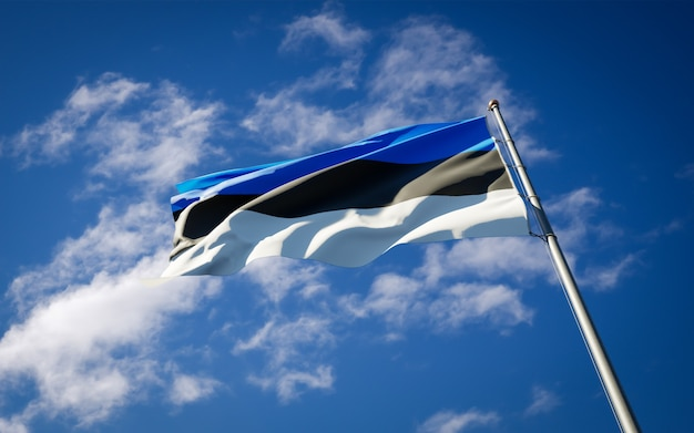 Beautiful national state flag of estonia fluttering on blue sky