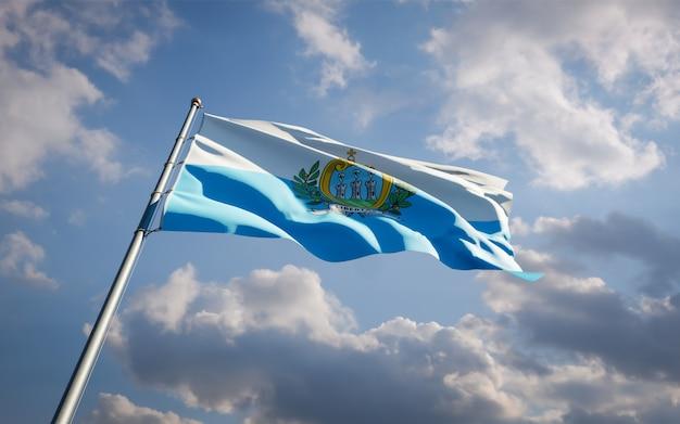 青い空に舞うサンマリノの美しい国民国家の旗