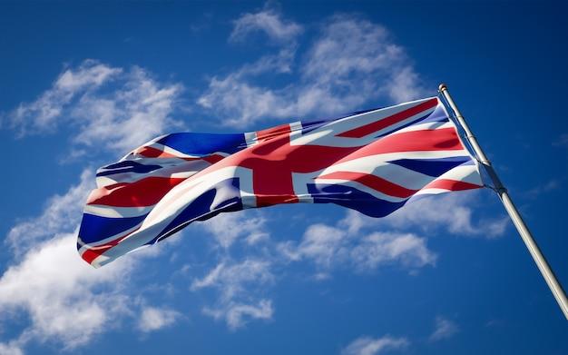 Красивый национальный государственный флаг великобритании развевается на голубом небе