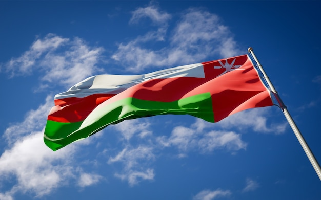 Beautiful national state flag of oman fluttering on blue sky