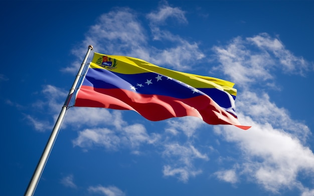 Beautiful national state flag of venezuela fluttering on blue sky