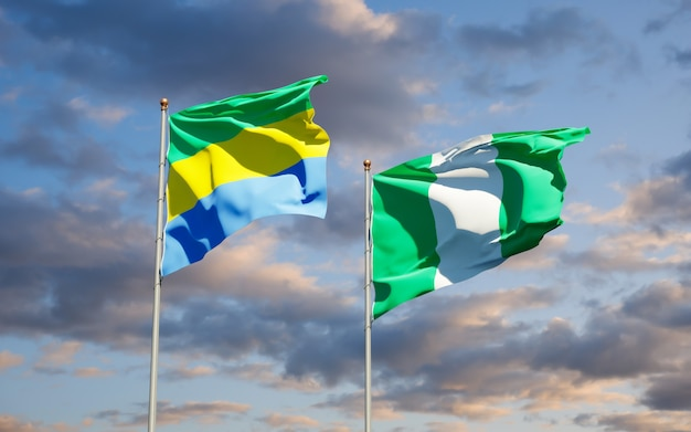 Beautiful national state flags of gabon and nigeria together on blue sky