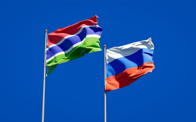 Beautiful national state flags of gambia and russia together on blue sky. 3d artwork