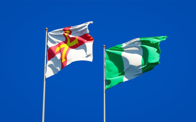 Beautiful national state flags of guernsey and nigeria together on blue sky