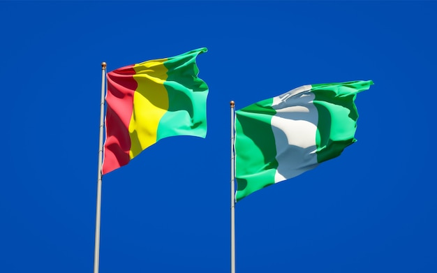 Beautiful national state flags of guinea and nigeria together on blue sky