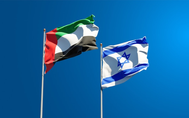 Beautiful national state flags of israel and united arab emirates uae together at the sky background.