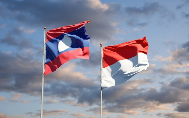 Beautiful national state flags of laos and indonesia together on blue sky