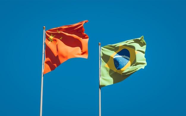 Красивые национальные государственные флаги бразилии и китая вместе на голубом небе