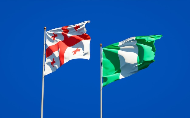 Красивые национальные государственные флаги грузии и нигерии вместе на голубом небе