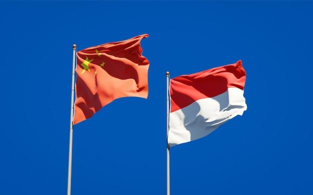 Красивые национальные государственные флаги индонезии и китая вместе на голубом небе