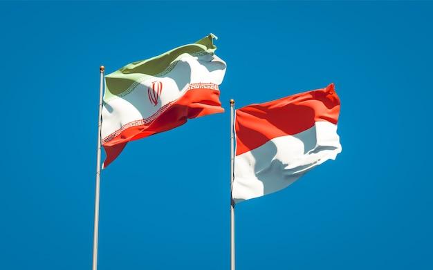 Красивые национальные государственные флаги ирана и индонезии вместе на голубом небе