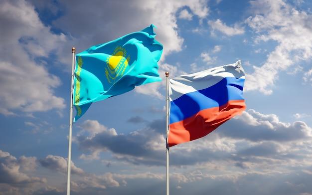 Красивые национальные государственные флаги казахстана и россии вместе на голубом небе. 3d изображение