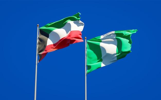 Красивые национальные государственные флаги кувейта и нигерии вместе на голубом небе