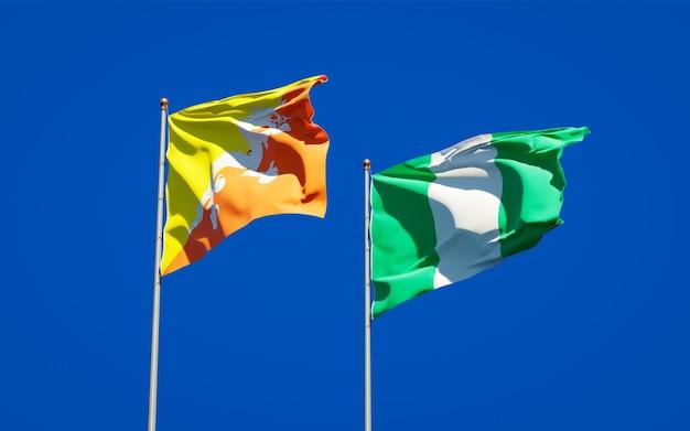 Красивые национальные государственные флаги нигерии и бутана вместе на голубом небе