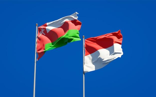 Красивые национальные государственные флаги омана и индонезии вместе на голубом небе