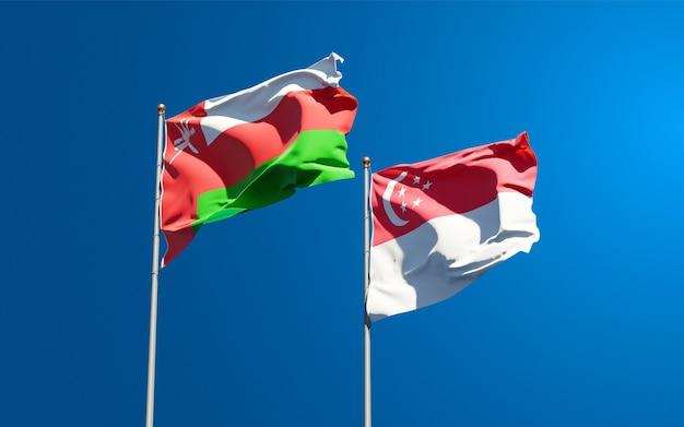 Красивые национальные государственные флаги омана и сингапура вместе