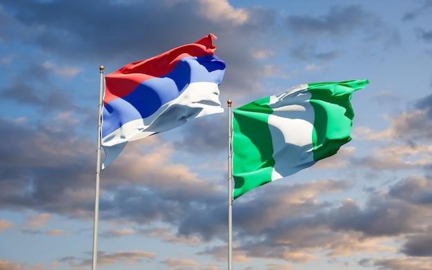 Красивые национальные государственные флаги республики сербской и нигерии вместе на голубом небе